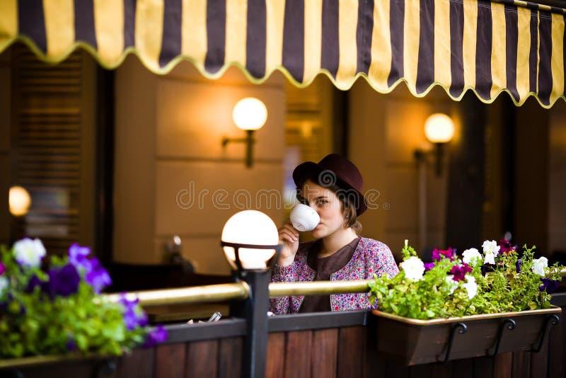 Den härliga unga kvinnan i en hatt sitter på en terrass i ett kafé, dricker te och ser kameran arkivfoto