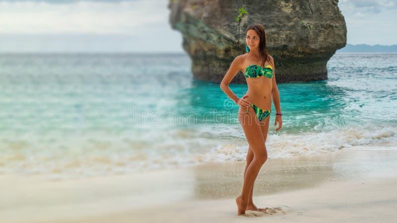 Den härliga unga kvinnan i en turkosbikini som poserar på stranden på bakgrunden av, vaggar Suddighet för kopieringsutrymme royaltyfri foto