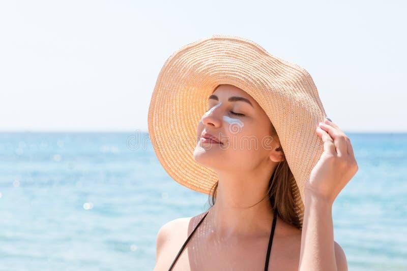 Den härliga unga kvinnan i hatt applicerar sunblock under hennes ögon och på hennes näsa som indier Gammal kvinna med hatten och  royaltyfria foton