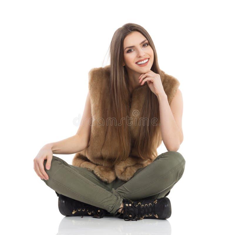 Den härliga unga kvinnan i pälsWaistcoat sitter med korsade ben arkivfoto