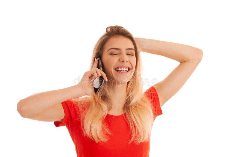 Den härliga unga kvinnan i röd t-skjorta talar på en smart telefon som isoleras över vit bakgrund - telefonpratstund arkivfoto