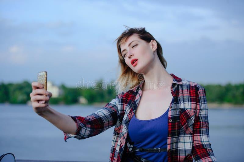 Den härliga unga kvinnan i regnet tar av på telefonen som är sinnlig och, stillar, lopp från regnet royaltyfri fotografi