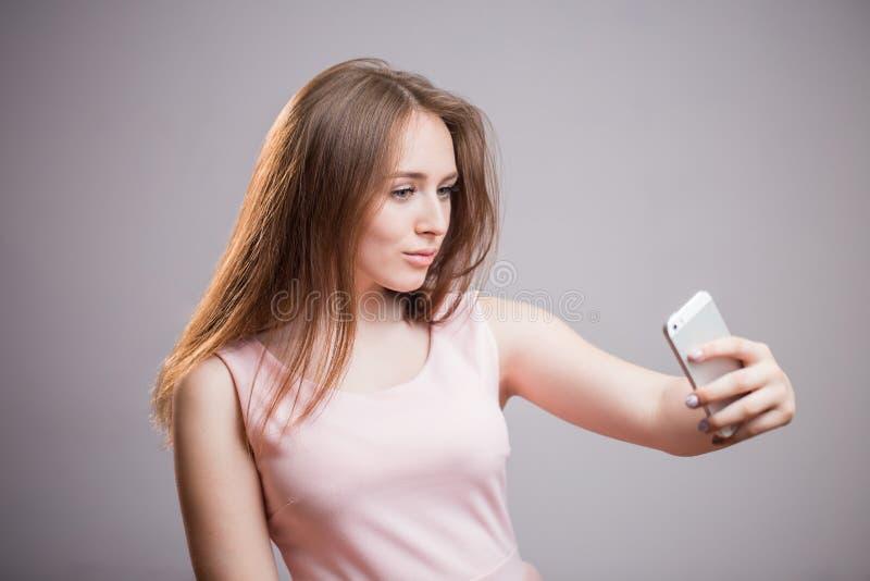 Den härliga unga kvinnan i rosa färger klär ta selfie på hennes smartphone och leenden på grå bakgrund arkivbilder