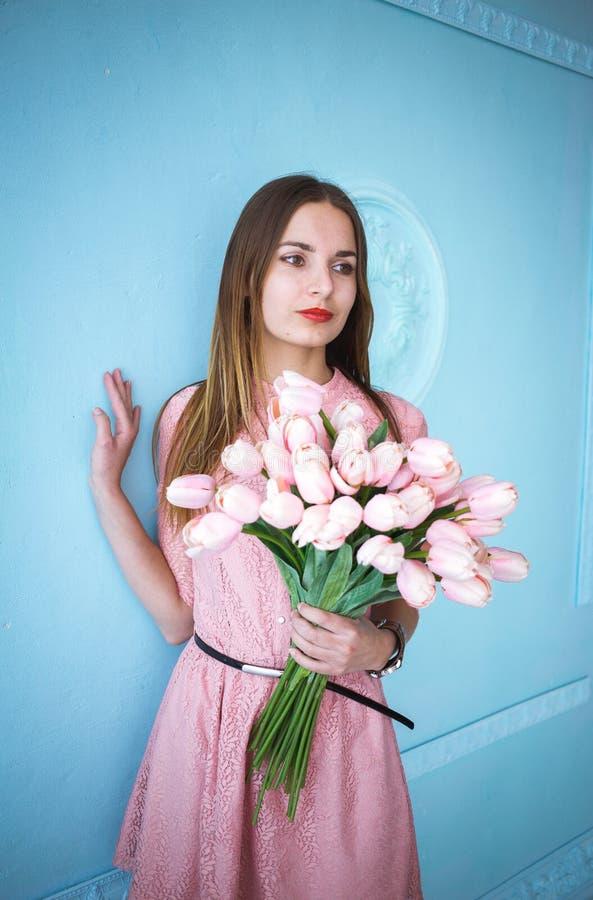 Den härliga unga kvinnan i rosa klänninginnehav i händer fjädrar tulpanblommabuketten på blå väggbakgrund royaltyfri fotografi