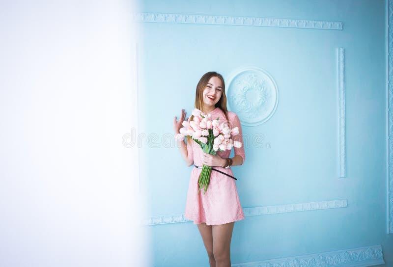 Den härliga unga kvinnan i rosa klänninginnehav i händer fjädrar tulpanblommabuketten på blå väggbakgrund royaltyfria bilder