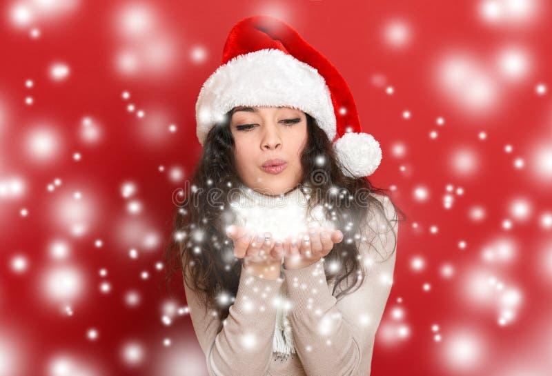 Den härliga unga kvinnan i santa hjälpredahatt som blåser snö från, gömma i handflatan, röd bakgrund royaltyfri foto