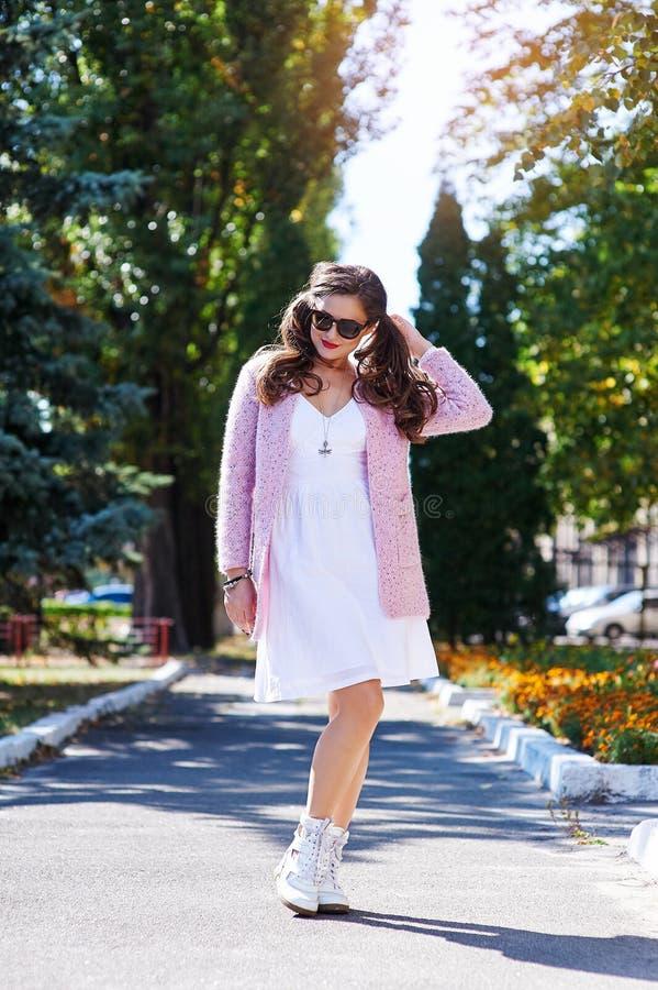 Den härliga unga kvinnan i solglasögon som går i sommar, parkerar royaltyfria foton