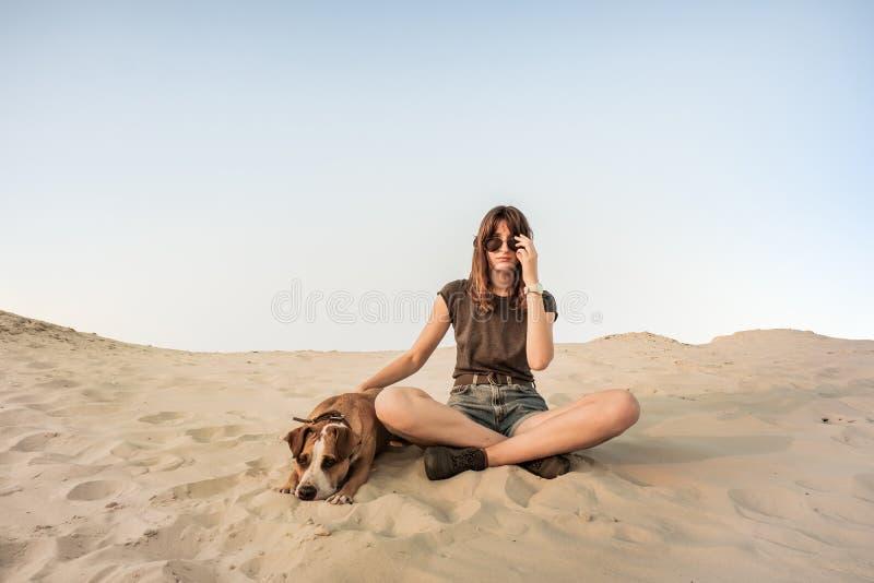 Den härliga unga kvinnan i solglasögon vilar med hunden på sandig beac royaltyfri foto