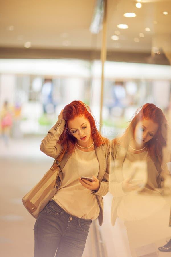 Den härliga unga kvinnan i staden, galleria är upptagen med hennes mobiltelefon och att tala som ler royaltyfri fotografi