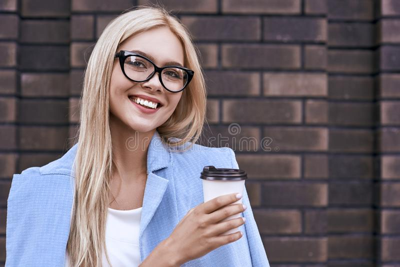 Den härliga unga kvinnan i tillfällig kläder och glasögon rymmer en kopp kaffe och leenden fotografering för bildbyråer