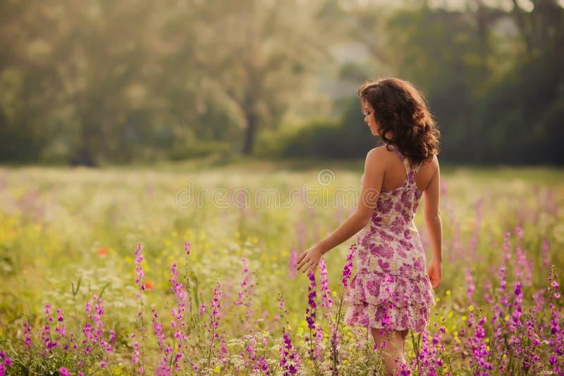 Den härliga unga kvinnan i vår blommar utomhus royaltyfri foto