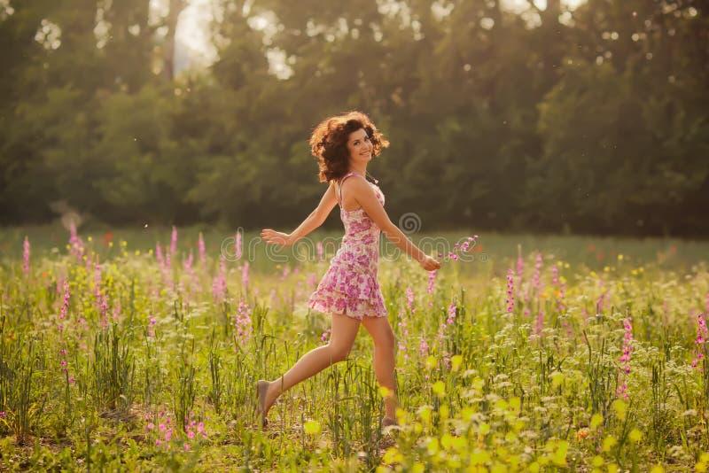 Den härliga unga kvinnan i vår blommar utomhus arkivfoto