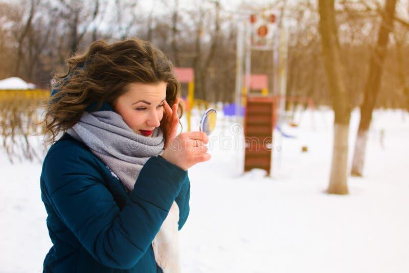 Den härliga unga kvinnan i vinter parkerar blickar i spegeln royaltyfria bilder