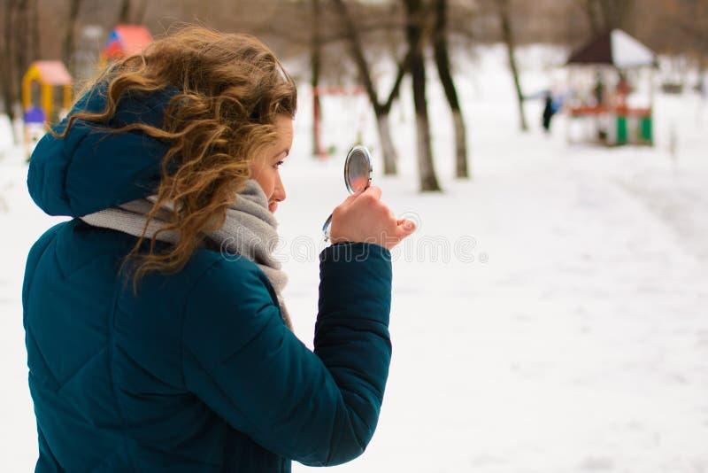 Den härliga unga kvinnan i vinter parkerar blickar i spegeln arkivfoto
