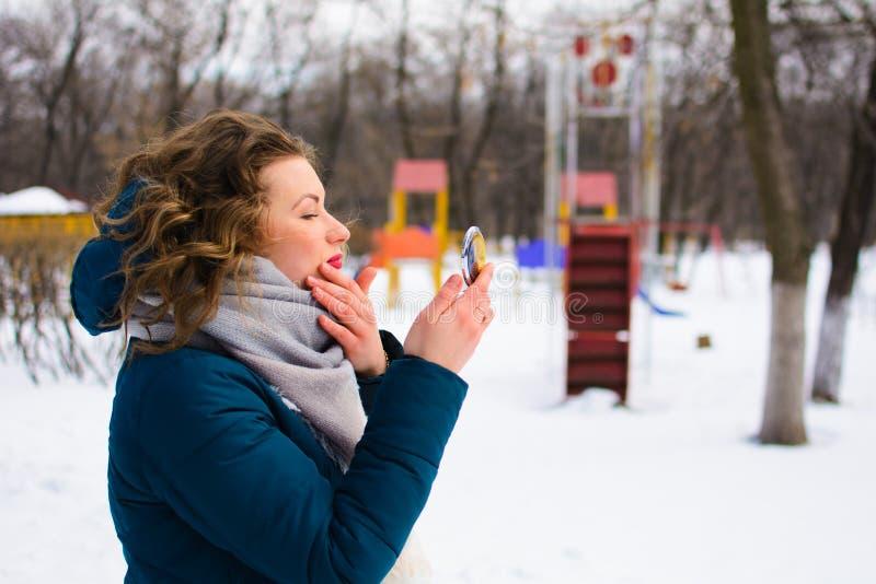 Den härliga unga kvinnan i vinter parkerar blickar i spegeln royaltyfri foto