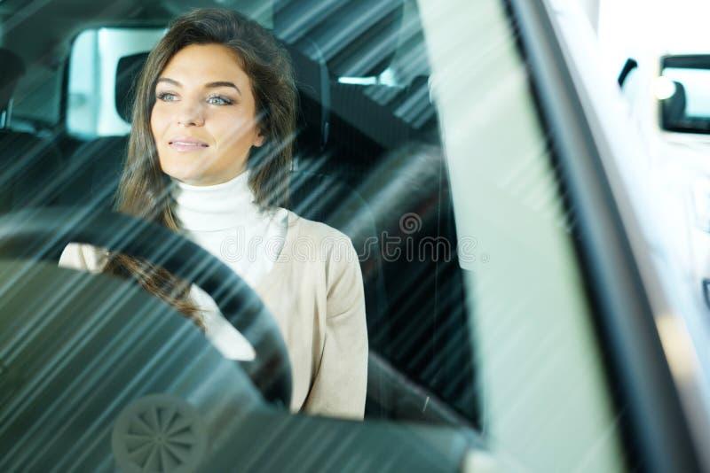 Den härliga unga kvinnan köper en bil i återförsäljaresalongen fotografering för bildbyråer