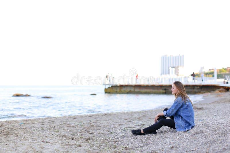 Den härliga unga kvinnan kopplar av sammanträde på stranden och tycker om siktsnolla royaltyfria bilder