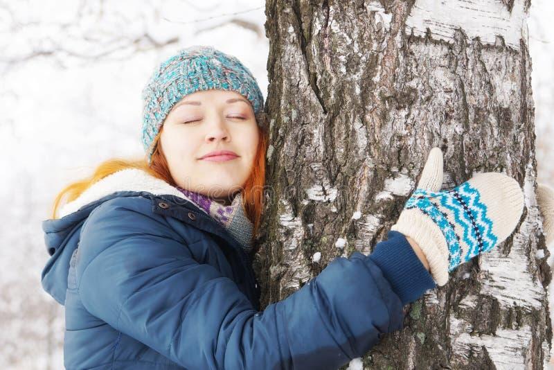 Den härliga unga kvinnan kramar björken i vinterskog royaltyfri bild