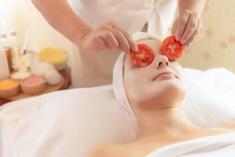 Den härliga unga kvinnan ligger ner på brunnsortsäng i brunnsortrum på brunnsortsalongen Massösen satte tomatskivor på kundögon f fotografering för bildbyråer