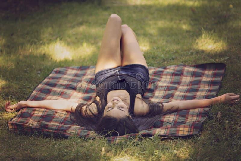 den härliga unga kvinnan ligger på en filt och kopplar av arkivfoton