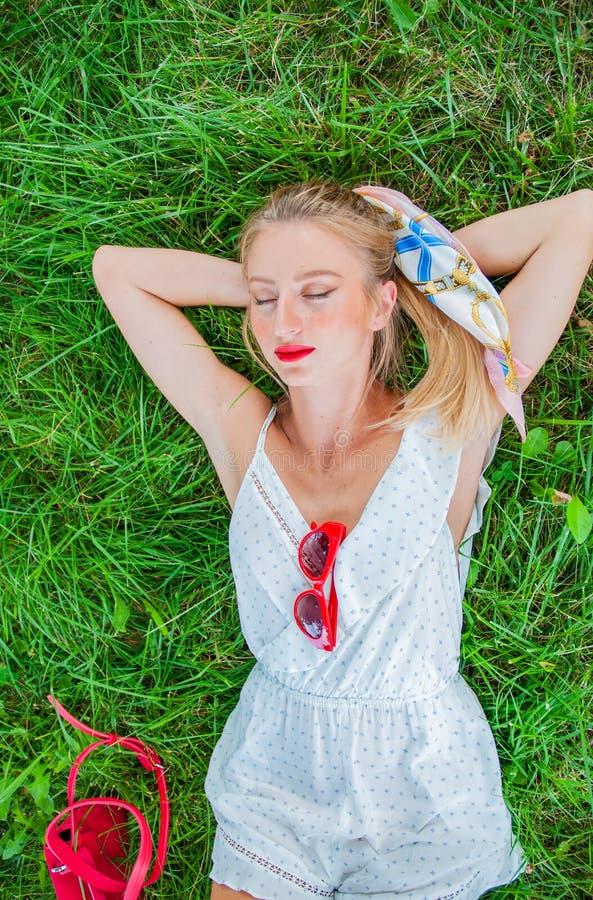 Den härliga unga kvinnan ligger på gräset i sommar royaltyfri foto
