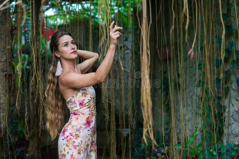Den härliga unga kvinnan lutar mot ett träd i regnskogen som bär den sexiga klänningen arkivbilder