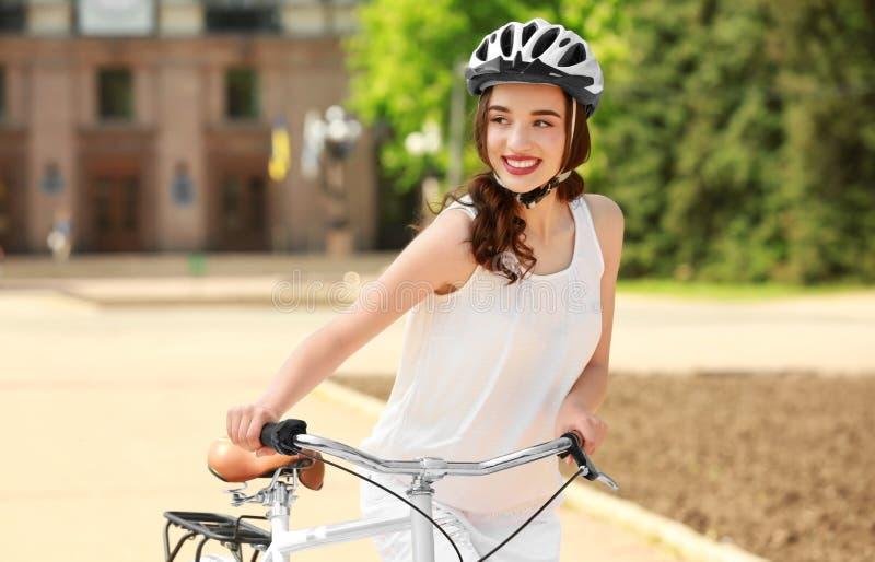 Den härliga unga kvinnan med cykeln och hjälmen parkerar in arkivfoto