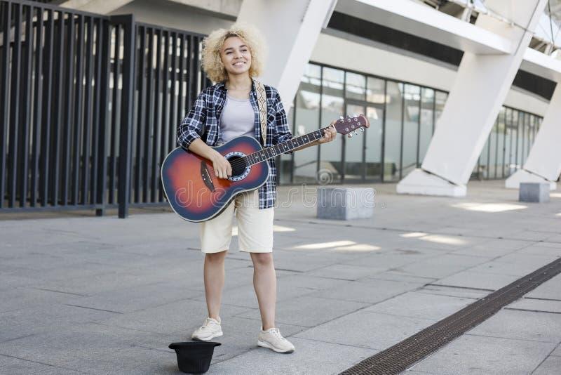 Den härliga unga kvinnan med en gitarr på gatan gör pengar royaltyfri bild