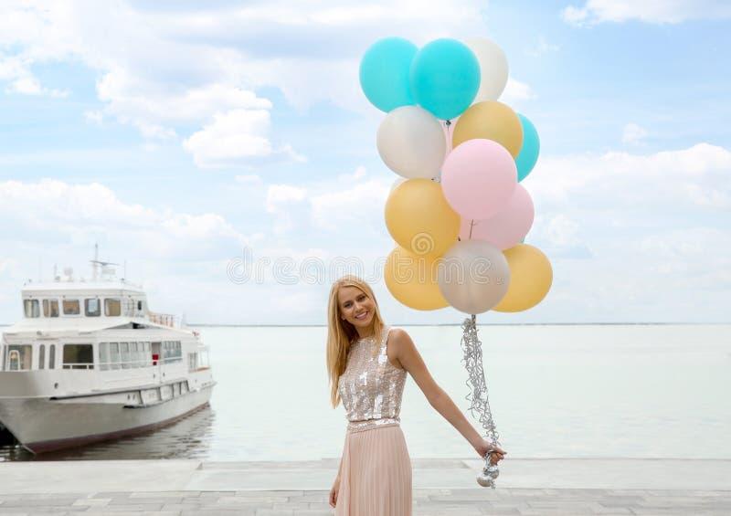 Den härliga unga kvinnan med gruppen av ballonger near sightfartyget arkivbild