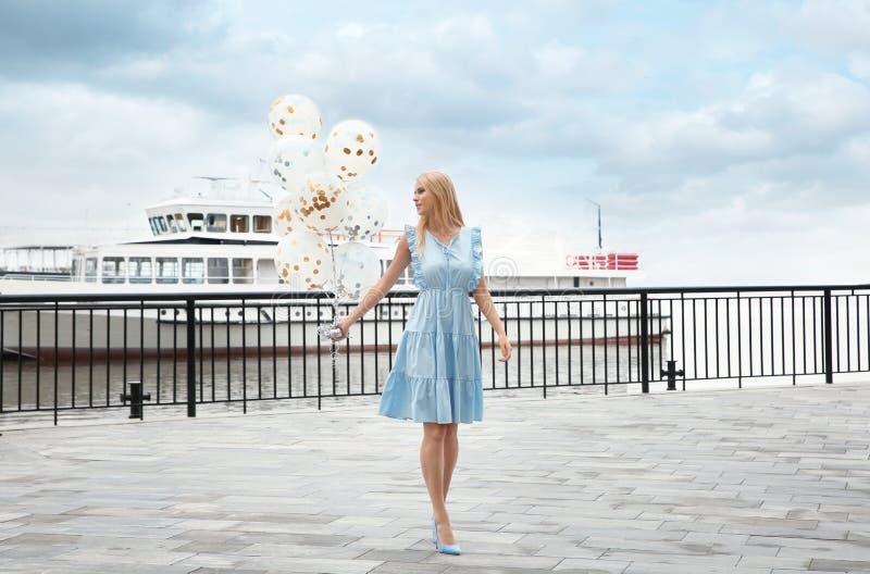 Den härliga unga kvinnan med gruppen av ballonger near sightfartyget arkivfoto
