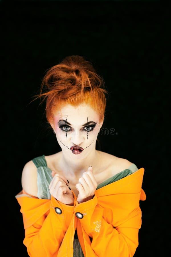 Den härliga unga kvinnan med halloween utgör och rött hår royaltyfri bild
