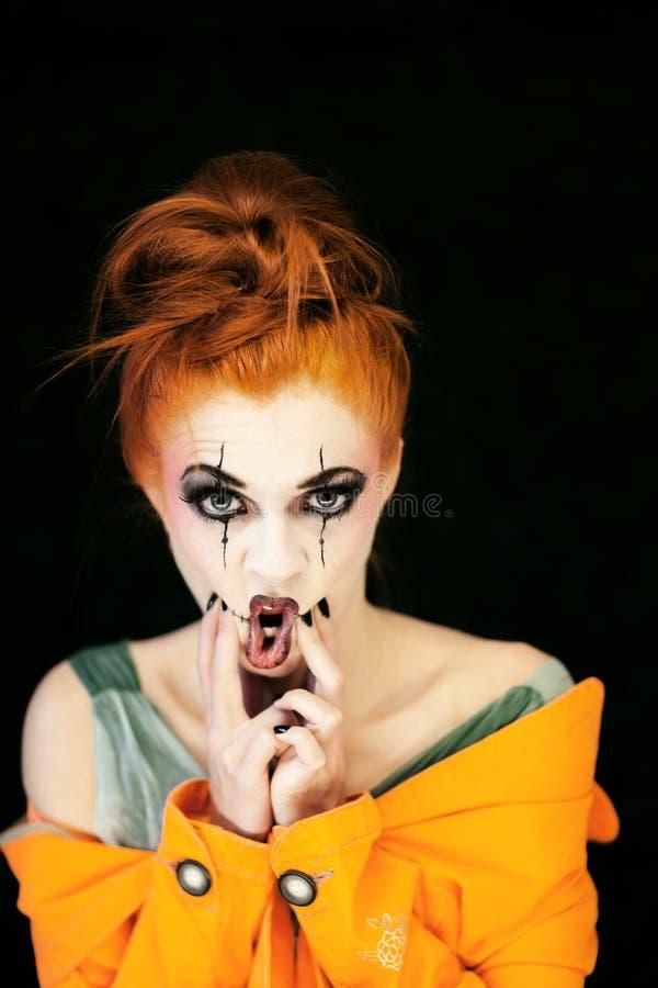 Den härliga unga kvinnan med halloween utgör och rött hår royaltyfri fotografi