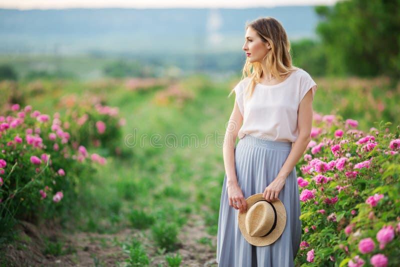 Den härliga unga kvinnan med hatten i händer poserar nära rosor i en trädgård arkivbild