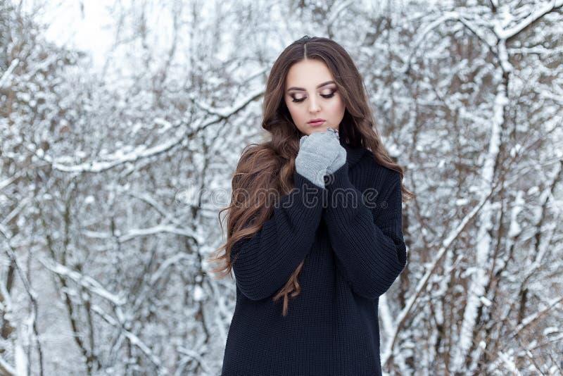Den härliga unga kvinnan med långt ledset ensamt för mörkt hår går i vinterträna i ett svart omslag och tumvanten arkivbilder