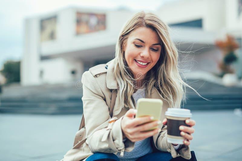 Den härliga unga kvinnan med mobil ringer arkivbild