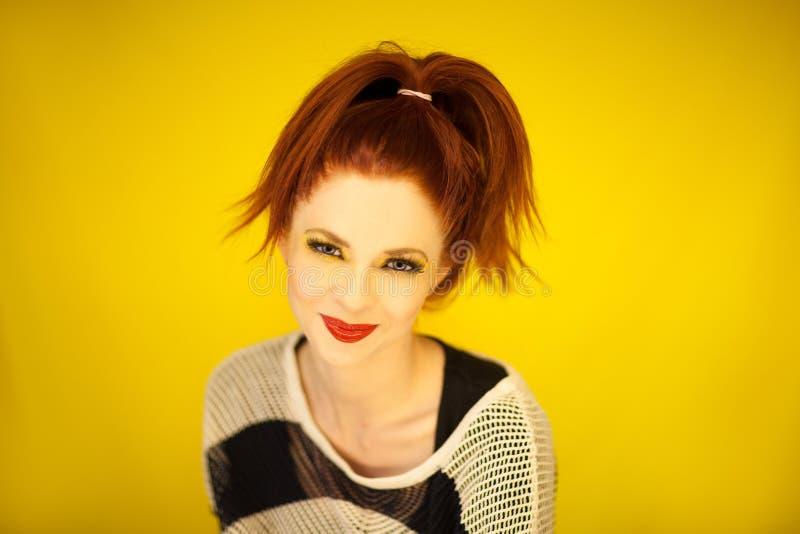 Den härliga unga kvinnan med rött hår och gör perfekt sminkmodeståenden royaltyfria foton
