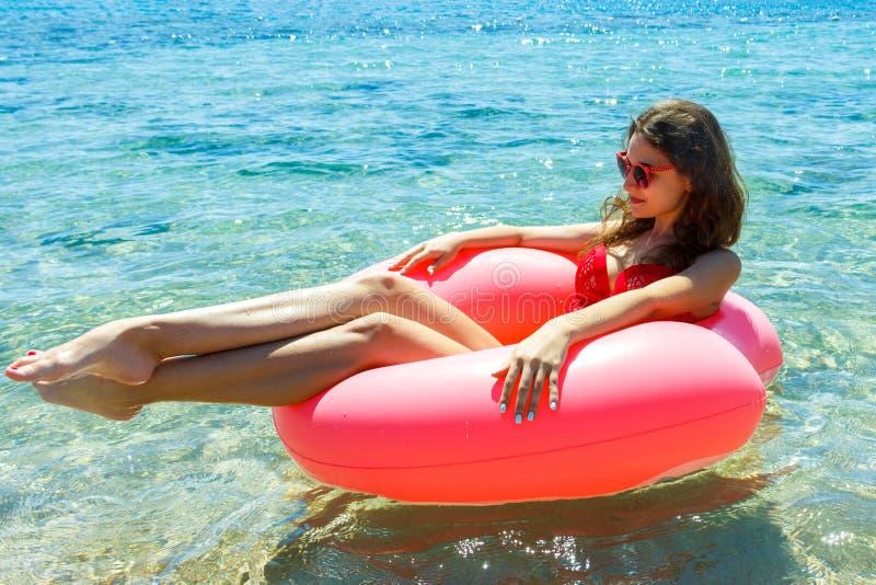 Den härliga unga kvinnan med rosa färger cirklar att koppla av i det blåa havet royaltyfri fotografi
