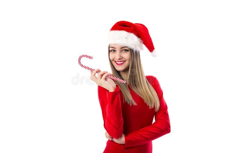 Den härliga unga kvinnan med den santa hatten som rymmer en festlig godis kan arkivbilder
