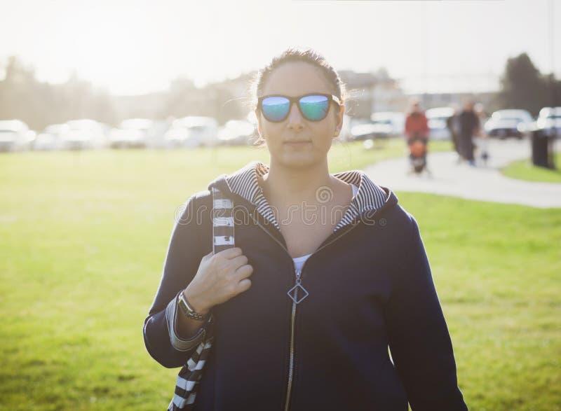 Den härliga unga kvinnan med solglasögon på parkerar royaltyfria foton
