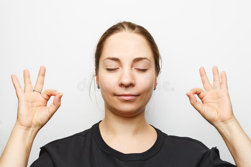 Den härliga unga kvinnan med stängda ögon som mediterar och kopplar av och att rymma händer och fingrar i mudra, undertecknar arkivfoton