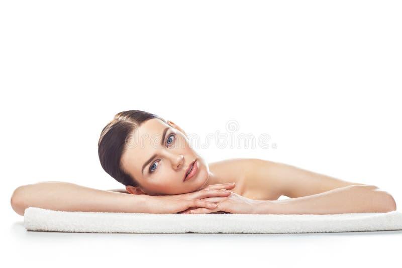 Den härliga unga kvinnan med sund ren hud vilar på en handduk royaltyfri foto