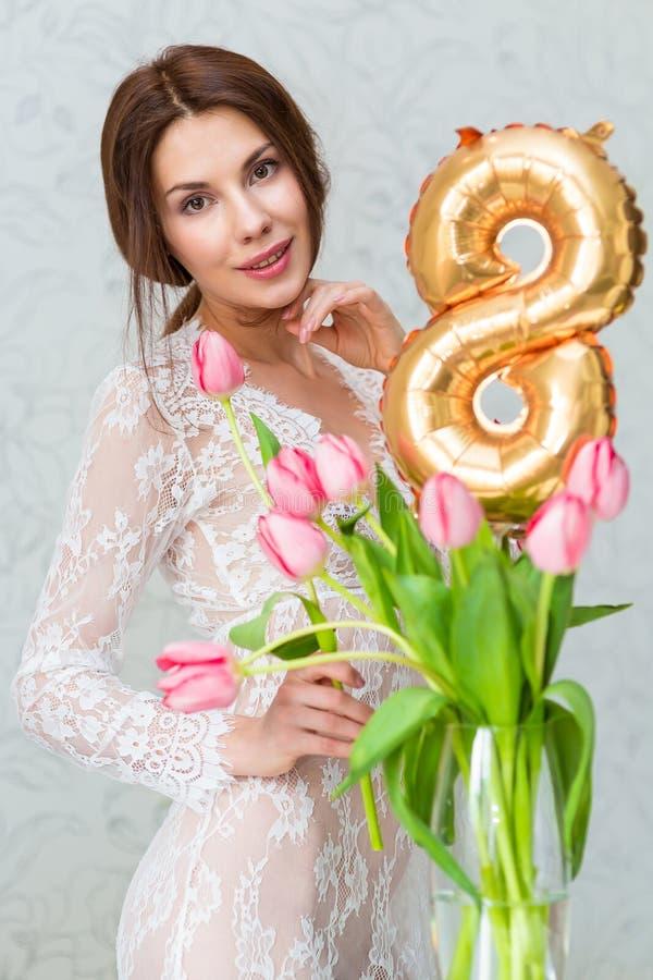 Den härliga unga kvinnan med vårtulpan blommar buketten Den lyckliga flickan som ler håll, blommar, den rosa tulpan Den ljusa ros arkivbilder