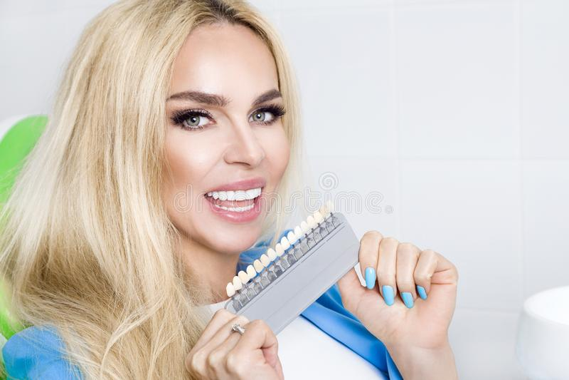 Den härliga unga kvinnan med vita och sunda tänder, ler hon Han har sunda och gjorde vit tänder och porslinfanér royaltyfria bilder