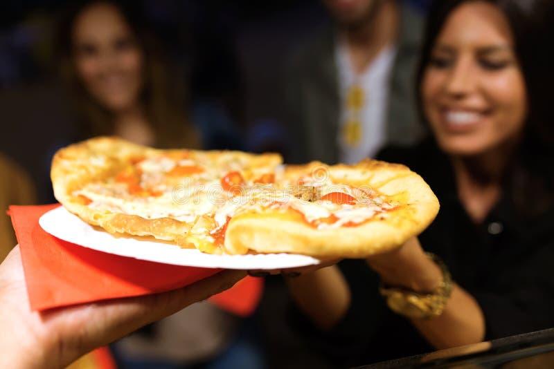 Den härliga unga kvinnan och hennes besöka för vänner äter marknaden och köpande pizza i gatan royaltyfri foto