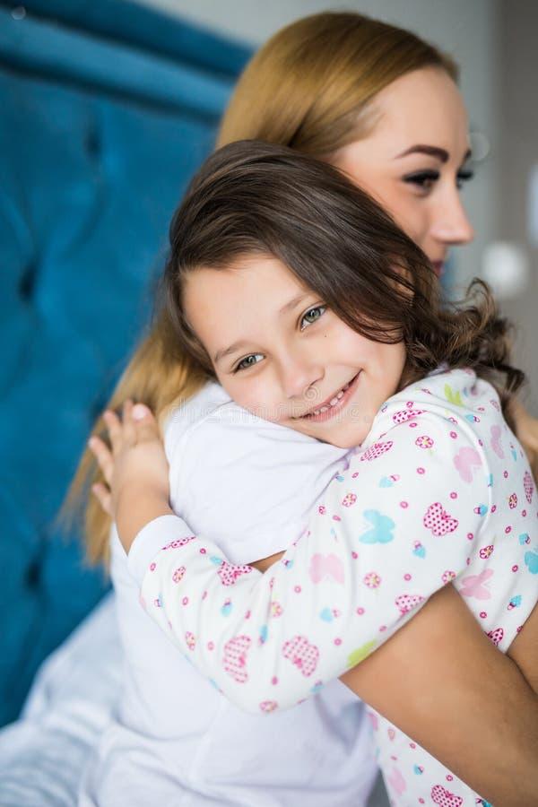 Den härliga unga kvinnan och hennes charmiga lilla dotter är krama och le på säng hemma fotografering för bildbyråer