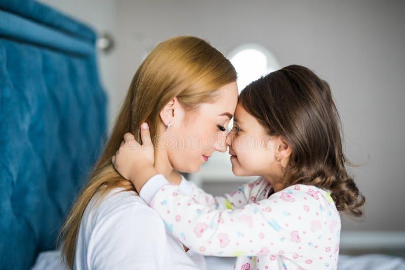 Den härliga unga kvinnan och hennes charmiga lilla dotter är krama och le på säng hemma royaltyfria foton