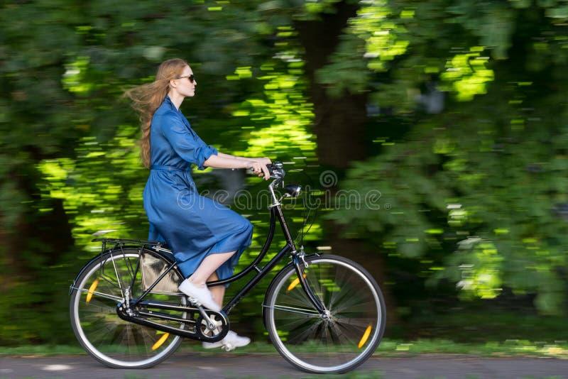 Den härliga unga kvinnan och tappning cyklar, sommar Röd hårflicka som rider den gamla svarta retro cykeln utanför i parkera fotografering för bildbyråer