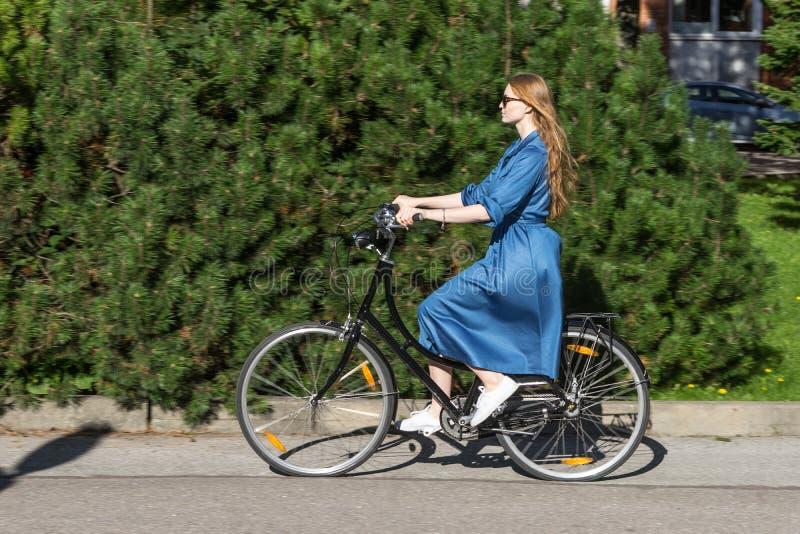 Den härliga unga kvinnan och tappning cyklar, sommar Röd hårflicka som rider den gamla svarta retro cykeln utanför i parkera arkivfoto