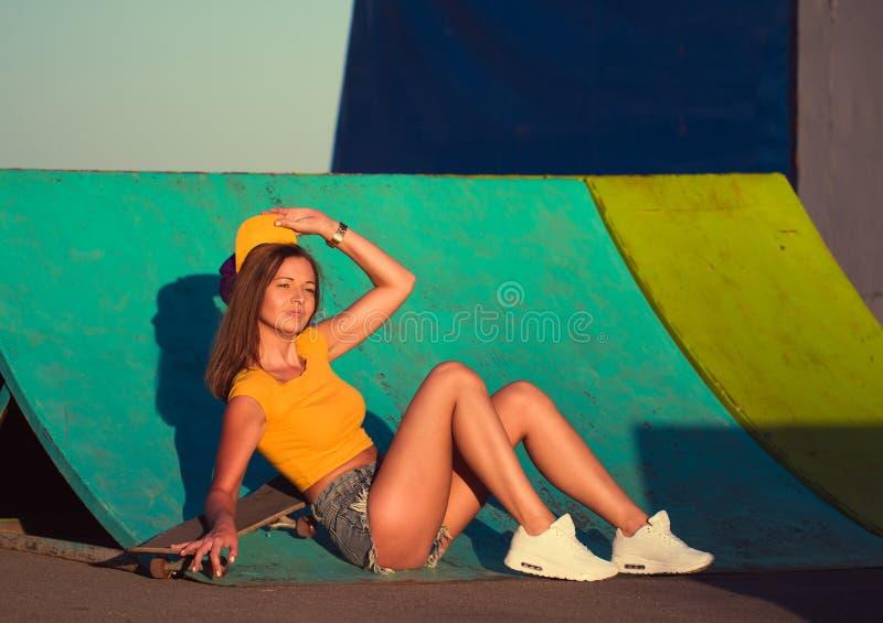 Den härliga unga kvinnan på en skateboard på skridskon parkerar royaltyfri foto