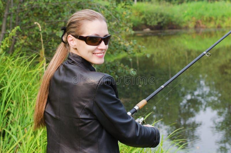 Den härliga unga kvinnan på fiske royaltyfri foto
